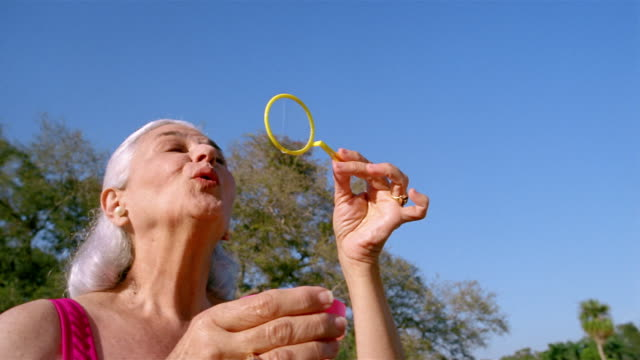 low angle medium shot senior woman blowing bubbles - low angle view stock videos & royalty-free footage
