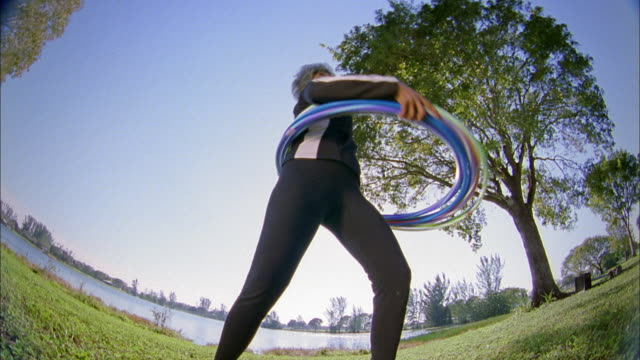 Low angle medium shot senior woman gyrating w/hula hoops