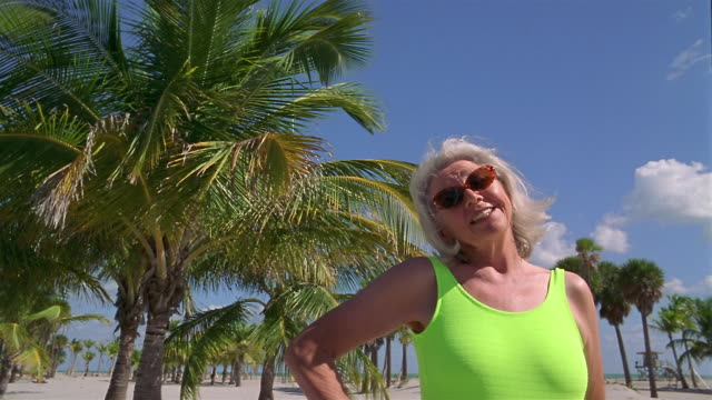 low angle medium shot senior woman smiling at cam with palm trees and blue sky in background - low angle view stock videos & royalty-free footage