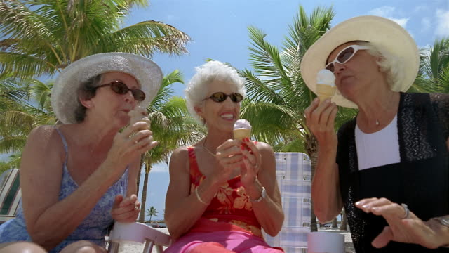 Low angle medium shot senior women eating ice cream cones with palm trees in background / Miami, Florida