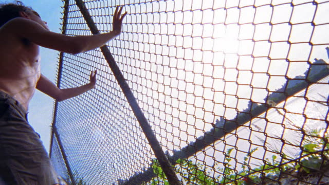 low angle medium shot shirtless man stretching against chain link fence / central park, nyc - shirtless stock videos & royalty-free footage