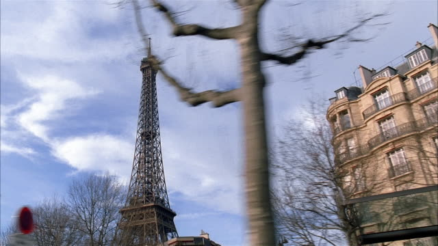 low angle medium shot side car point of view traveling on city street with eiffel tower in background / paris - eiffelturm stock-videos und b-roll-filmmaterial