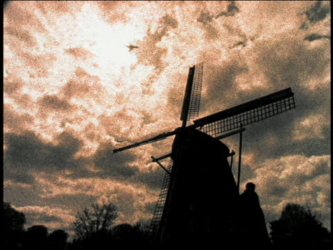 stockvideo's en b-roll-footage met low angle medium shot silhouetted people walking next to windmill with airplane flying above / holland - hoog contrast