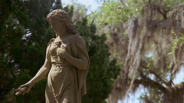 low angle medium shot statue of woman on tomb in bonaventure cemetery / savannah, georgia - ゴシック様式点の映像素材/bロール