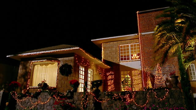 Low angle medium shot suburban house with christmas lights / room lights turning off at night