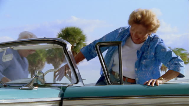 low angle medium shot three senior women getting into vintage car with palm trees and blue sky in background - old convertible stock videos & royalty-free footage