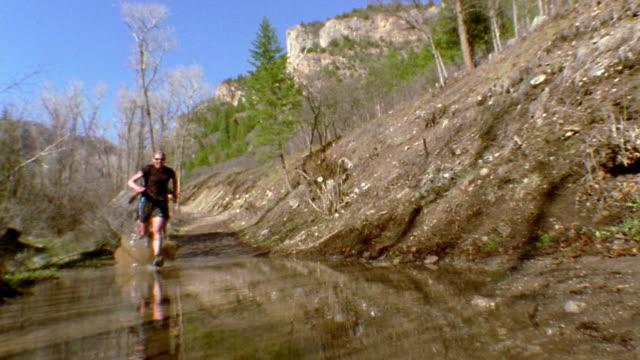 Low angle medium shot three women wearing sunglasses running through muddy water / Colorado
