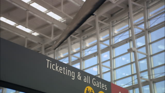 Low angle medium shot ticketing sign in airport/ Seattle