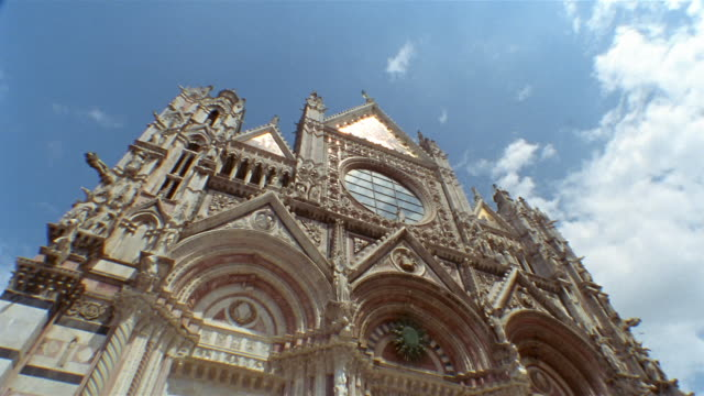 vidéos et rushes de low angle medium shot tilt down detail of front fa?ade of the duomo in siena / tuscany, italy - fronton
