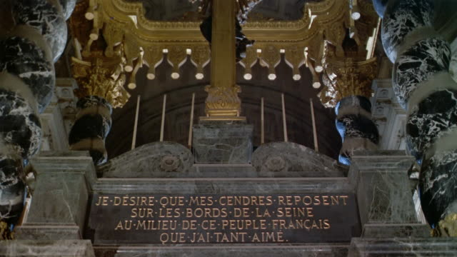 low angle medium shot tilt down from ceiling to plaque over doors opening to stairway to coffin at napoleon's tomb / paris - sarg stock-videos und b-roll-filmmaterial