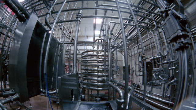 Low angle medium shot tilt down network of pipes and basin of water at a water purification plant / San Antonio, Texas