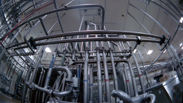 Low angle medium shot tilt down network of pipes at a water purification plant / San Antonio, Texas