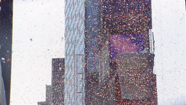 low angle medium shot tilt down ticker tape falling over times square at broadway and west 45 st. / new york city - ticker tape stock videos and b-roll footage