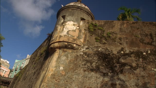 Low angle medium shot tilt up corner lookout tower of fortified wall of San Cristobal / Old San Juan, Puerto Rico