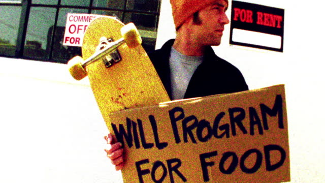 Low angle medium shot tilt up man standing outdoors with skateboard and sign reading 'will program for food' / San Francisco