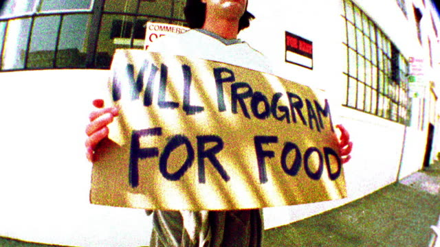 """Low angle medium shot tilt up man stands outdoors with sign reading """"will program for food"""" / San Francisco"""