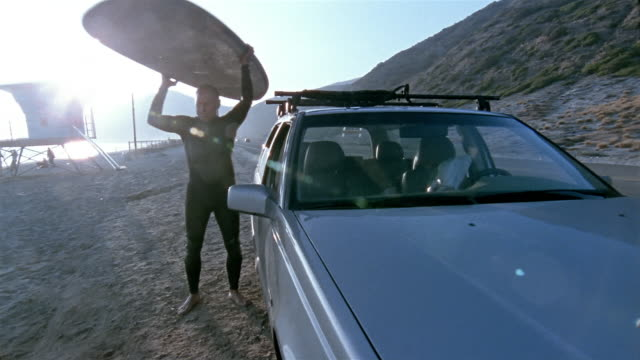 low angle medium shot tilt up senior man talking surfboard off roof of car / pan walking towards water - 取り除く点の映像素材/bロール