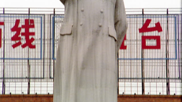 Low angle medium shot tilt up statue of Mao Zedong (Mao Tse Tung) in front of Chengdu Trade Palace / China