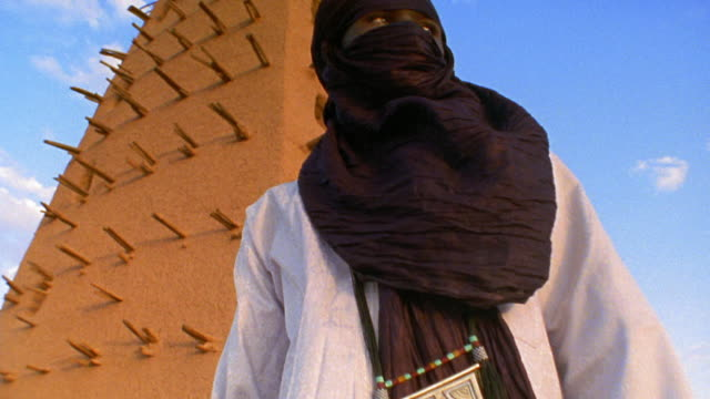 Low angle medium shot tilt up Tuareg tribesman with shesh headdress standing in front of Agadez Mosque / Niger