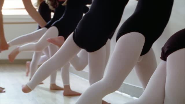 vídeos y material grabado en eventos de stock de low angle medium shot tilt up young girls wearing leotards practicing arabesques at the barre in ballet class / teacher positioning girl's leg - barra de deportes