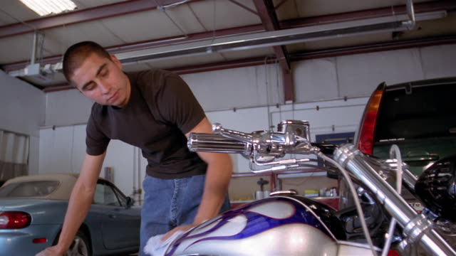 low angle medium shot tilt up young man polishing motorcycle in garage - polishing stock videos & royalty-free footage