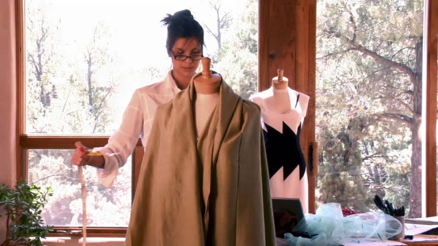 low angle medium shot tilt up young woman clothing designer working with and measuring fabric on dressmaker's model/ santa fe, new mexico - fashion designer stock videos & royalty-free footage