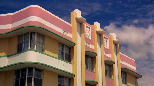low angle medium shot time lapse clouds in blue sky over art deco pastel-colored building in miami / florida - アールデコ点の映像素材/bロール