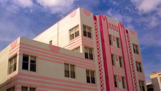 low angle medium shot time lapse clouds in blue sky over art deco pastel-colored building in miami / florida - pastel stock videos & royalty-free footage