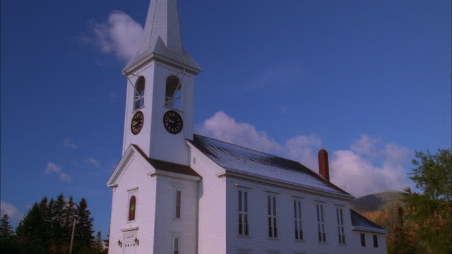 Low angle medium shot time lapse clouds moving behind church / New Hampshire