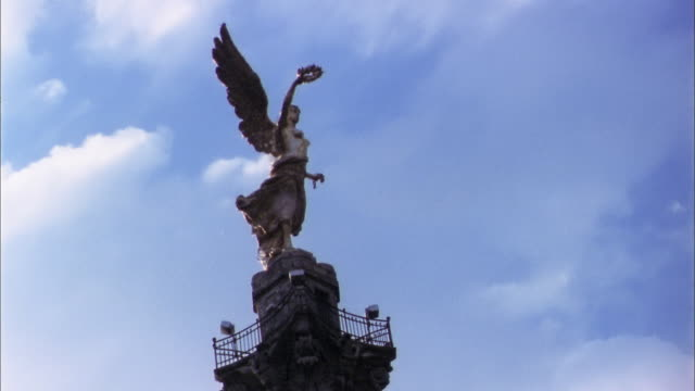 Low angle medium shot time lapse clouds passing over Independence Monument angel statue / Mexico City