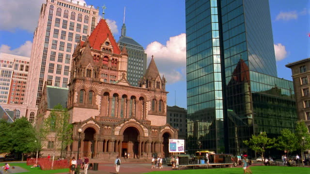Low angle medium shot time lapse clouds rolling behind John Hancock Building and Trinity Church in Copley Square / Boston, Massachusetts