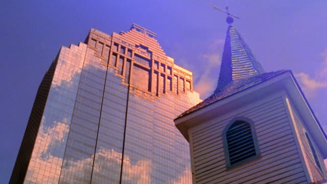 Low angle medium shot time lapse clouds rolling over office building and steeple with weather vane in Houston / Texas