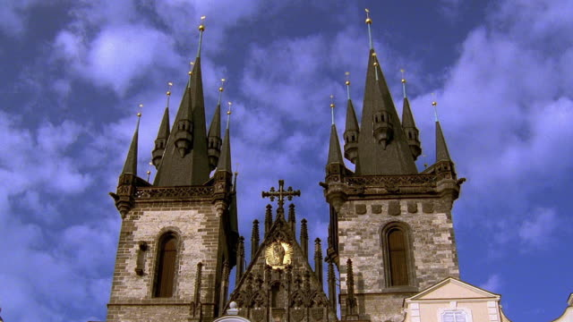 vídeos de stock, filmes e b-roll de low angle medium shot time lapse clouds rolling over spires of tyn church / prague, czech republic - stare mesto