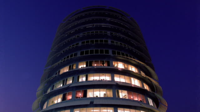 Low angle medium shot time lapse lights turning on in Capitol Records building at night / Los Angeles, California