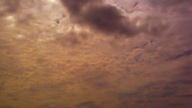 low angle medium shot time lapse two layers of clouds moving in different directions with orange sunlight from sunset / hawaii - 1985 stock videos & royalty-free footage