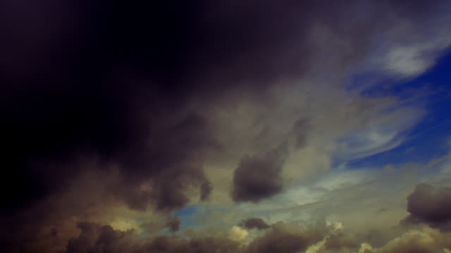 vidéos et rushes de low angle medium shot time lapse white clouds becoming dark in blue sky - sparklondon