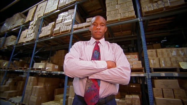 Low angle medium shot tracking shot Black businessman rotating in aisle of warehouse