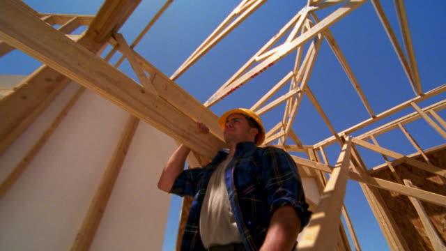 vídeos y material grabado en eventos de stock de low angle medium shot tracking shot construction worker carrying wooden beam while walking through frame of house / texas - un solo hombre de mediana edad