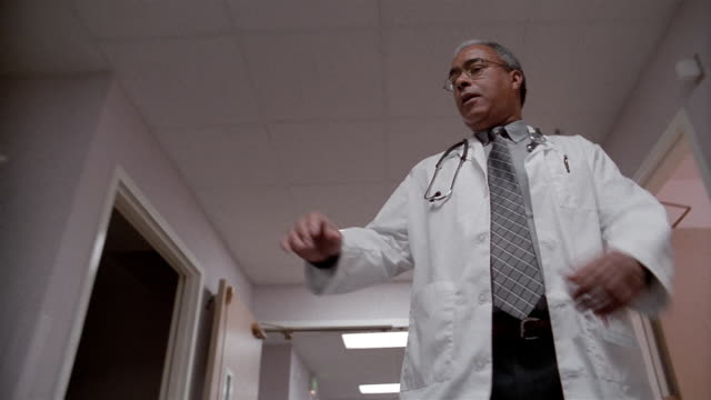 low angle medium shot tracking shot doctor walking down hallway and signing clipboard handed to him by nurse - african american ethnicity stock videos & royalty-free footage