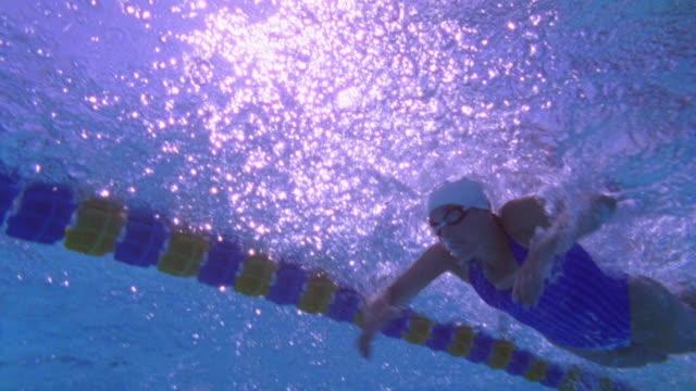 vídeos de stock, filmes e b-roll de low angle medium shot tracking shot female swimmer doing butterfly stroke over camera / california - touca de natação
