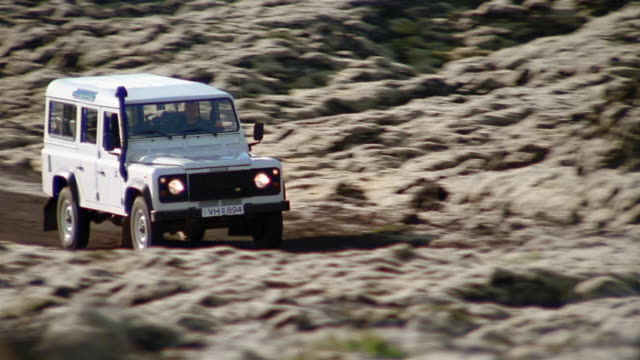 Low angle medium shot tracking shot man driving Land Rover through lava field near the Blue Lagoon (Blaa Loninu) / Iceland