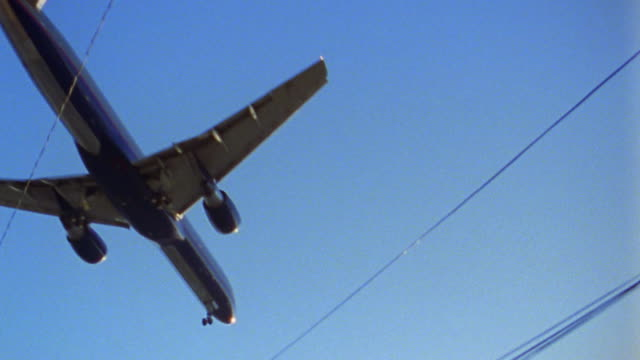low angle medium shot tracking shot plane flying over residential area w/power lines in blue sky - power line stock videos & royalty-free footage
