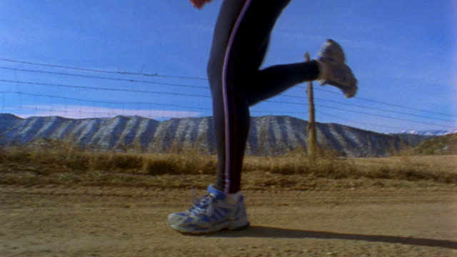 stockvideo's en b-roll-footage met low angle medium shot tracking shot woman running on country road w/mountains and fence in background / newcastle, colorado, usa - lycra