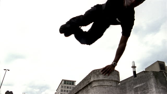 low angle medium shot two freerunner jumping off ledge on roof - city life stock videos & royalty-free footage