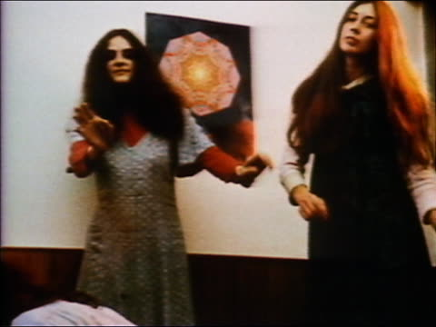 vídeos de stock e filmes b-roll de 1972 low angle medium shot two hippie women with long hair dancing - hippie