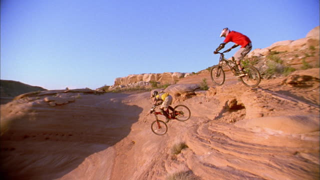 low angle medium shot two men jumping on mountain bikes / high angle riding downhill - moab utah stock-videos und b-roll-filmmaterial