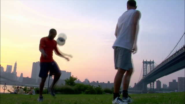 low angle medium shot two men passing soccer ball back and forth in park with manhattan skyline in background / dumbo, brooklyn, new york - stunt stock videos & royalty-free footage