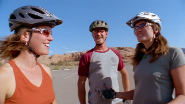 low angle medium shot two women and man wearing bike helmets + sunglasses laughing + talking - maschio con gruppo di femmine video stock e b–roll