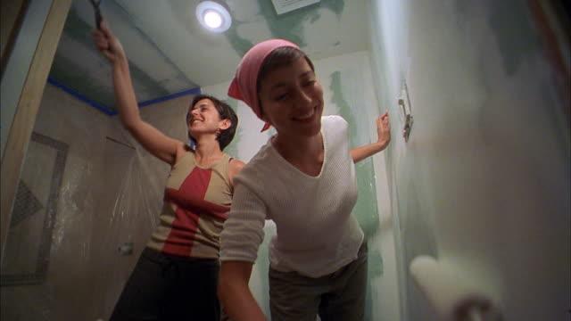 Low angle medium shot two women painting bathroom