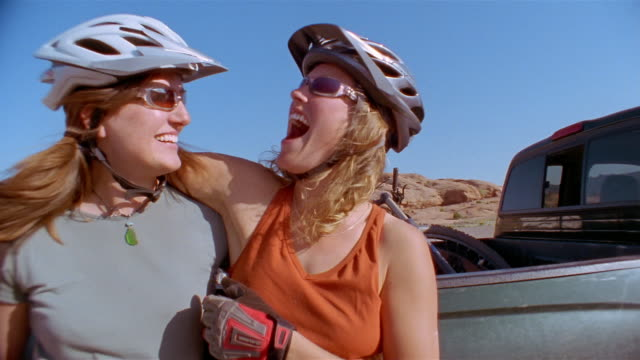 Low angle medium shot two women wearing bike helmets hugging and laughing + looking at CAM